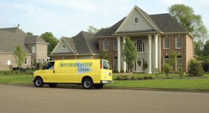 Yellow ServiceMaster van parked in front of a house
