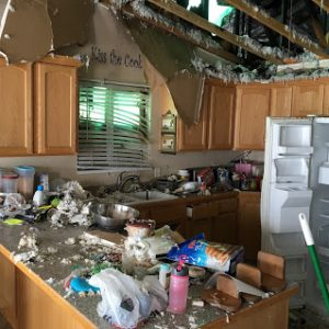 Kitchen with fire damage and lots of debris collapsed on countertops