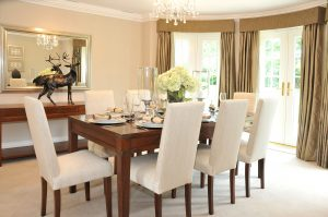 8 white chairs around a dining table with a crystal chandelier hanging above