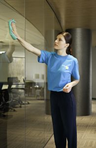 woman cleaning glass in an office