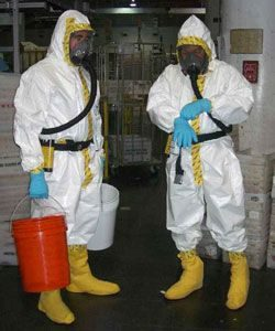 two technicians in hazmat suits with gloves, boots and full-face respirators