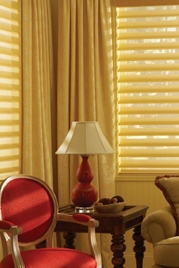 drapes and mini blinds hanging in a room with a red chair, end table and lamp