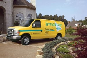 ServiceMaster yellow van parked in front of a home