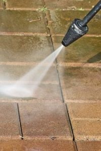 close up of a nozzle pressure washing a paver walkway
