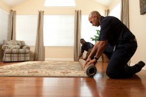 two technicians rolling up an area rug