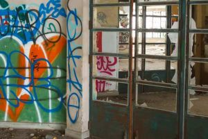 graffiti on a concrete wall and pillar and broken glass on doors