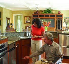 Woman with technician in kitchen inspecting cabinets