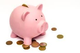 Piggy bank with change around it